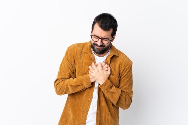 Bel homme de race blanche avec barbe portant une veste en velours côtelé sur blanc ayant une douleur au cœur