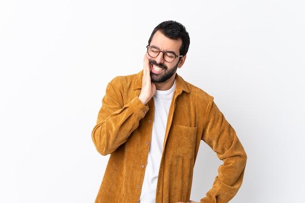 Bel homme de race blanche avec barbe portant une veste en velours côtelé sur un mur blanc isolé avec des maux de dents