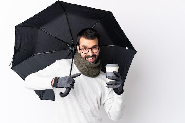 Bel homme de race blanche avec barbe tenant un parapluie et un café à emporter sur le mur blanc