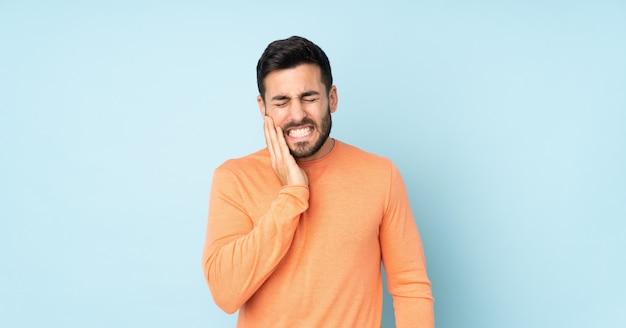 Bel homme de race blanche avec des maux de dents sur le mur bleu