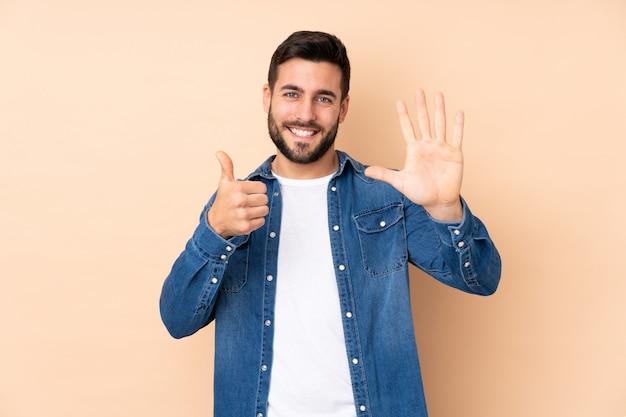 Bel homme de race blanche sur mur beige comptant six avec les doigts