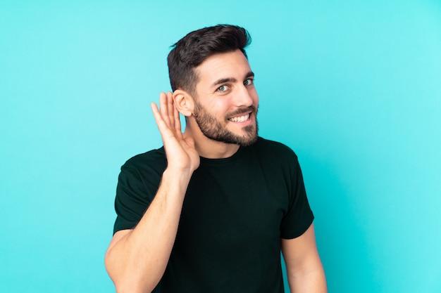 Bel homme de race blanche sur le mur bleu en écoutant quelque chose en mettant la main sur l'oreille