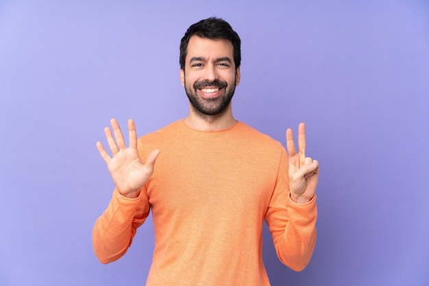 Bel homme de race blanche sur mur violet comptant sept avec les doigts