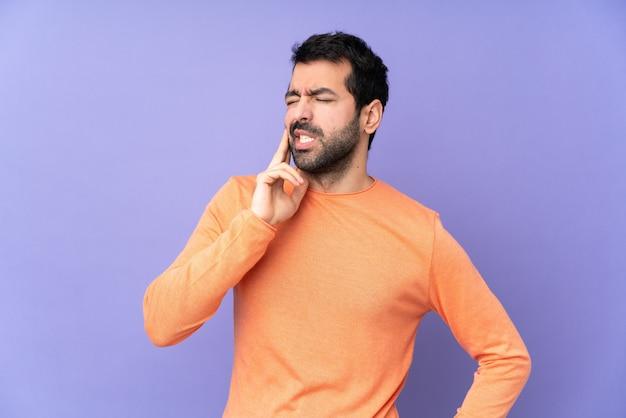 Bel homme de race blanche sur mur violet isolé avec maux de dents