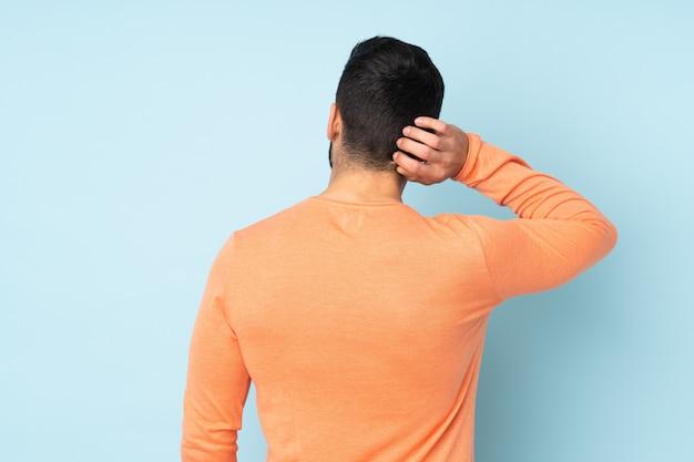 Bel homme de race blanche en position arrière et en réfléchissant sur le mur bleu isolé