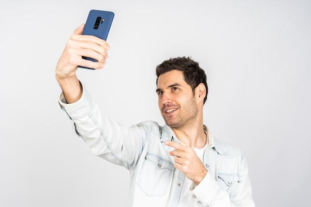 Bel homme de race blanche tenant un téléphone et faisant un selfie