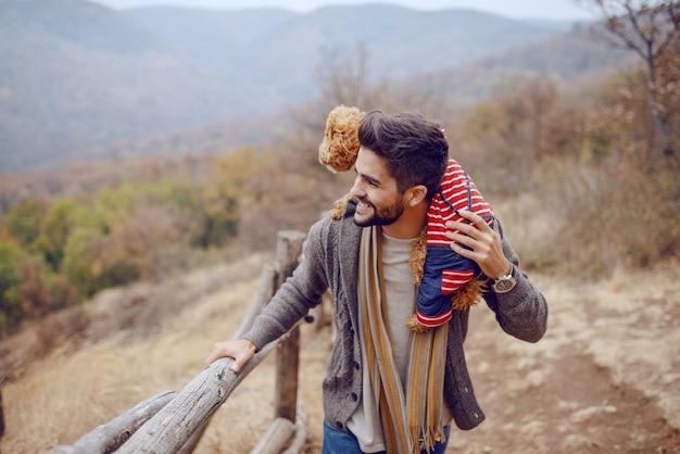 Bel homme de race mixte barbu habillé décontracté marchant dans la nature à l'automne et portant son caniche abricot sur les épaules.