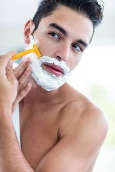 Bel homme rasant sa barbe dans la salle de bain