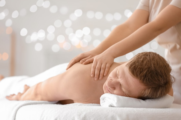 Bel homme recevant un massage dans un salon spa