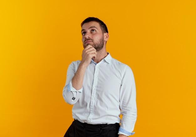 Bel homme réfléchi met la main sur le menton en levant isolé sur mur orange
