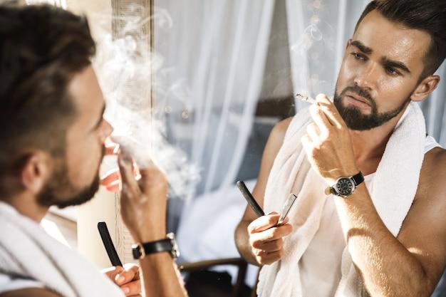Bel homme regardant dans le miroir, fumant une cigarette et se raser la barbe avec un rasoir droit