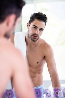 Bel homme regardant dans le miroir à la maison dans la salle de bain