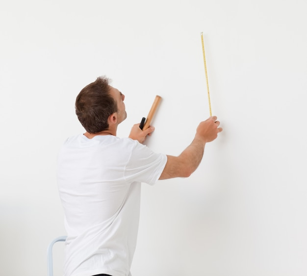 Bel homme en regardant un mur avec règle et outils
