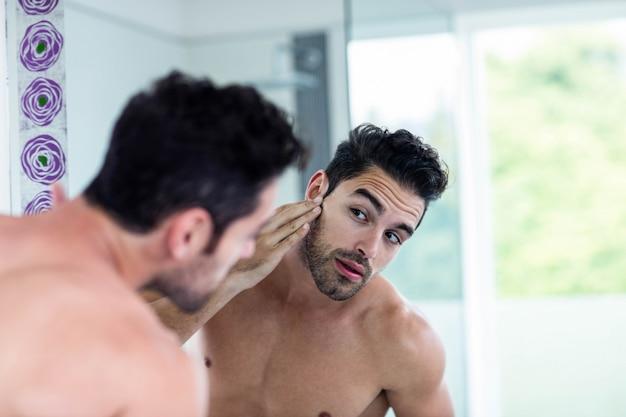 Bel homme regardant ses cheveux dans la salle de bain