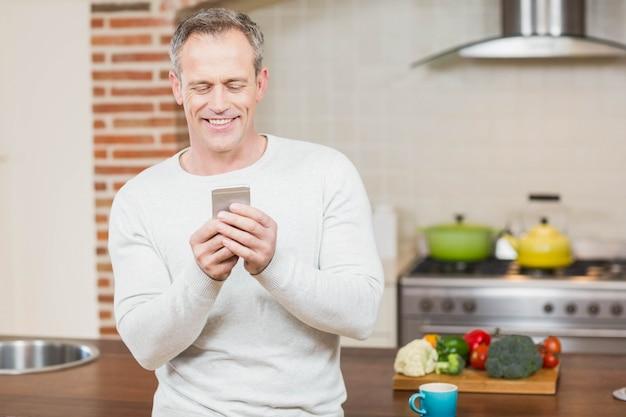 Bel homme regardant smartphone dans la cuisine