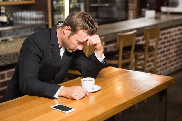 Bel homme regardant smartphone et prendre un café