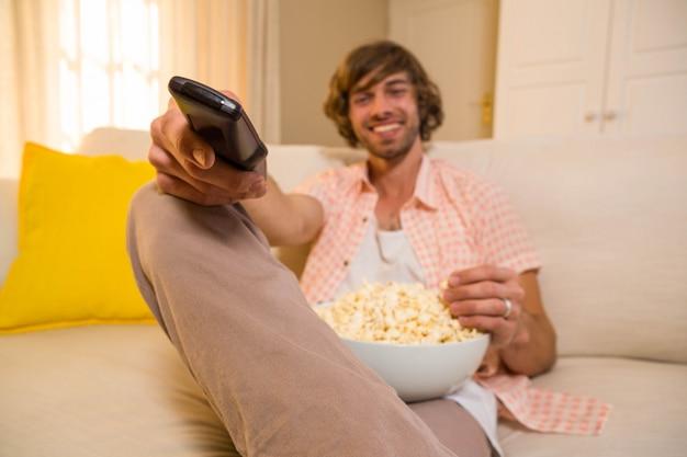 Bel homme en regardant la télévision et en mangeant du pop corn assis sur le canapé