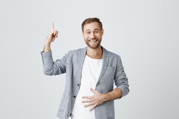 Bel homme en riant, pointant le doigt vers le haut