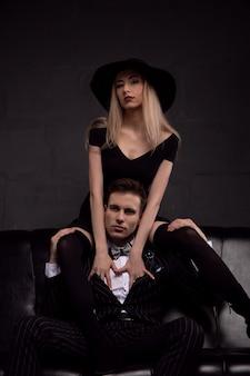 Un bel homme riche boit du whisky avec une maîtresse blonde le soir en basse lumière