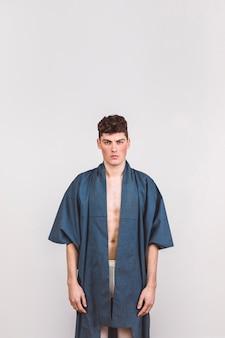 Bel homme en robe bleue avec un fond blanc