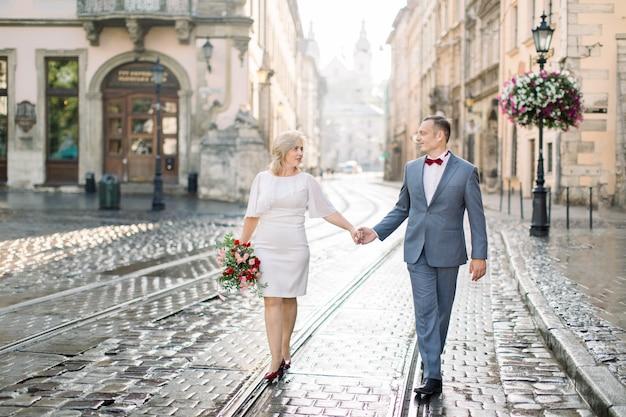 Bel homme romantique et belle femme, portant des vêtements élégants, profitant d'une promenade en ville. portrait d'un couple amoureux d'âge moyen heureux, se tenant la main, ayant un rendez-vous dans la ville antique