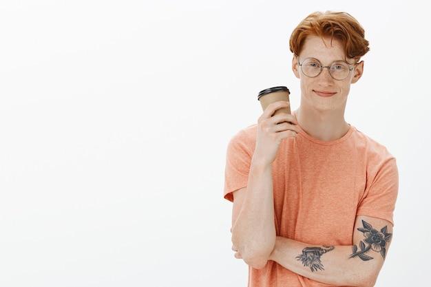 Bel homme rousse hipster dans des verres, boire du café et souriant avec désinvolture