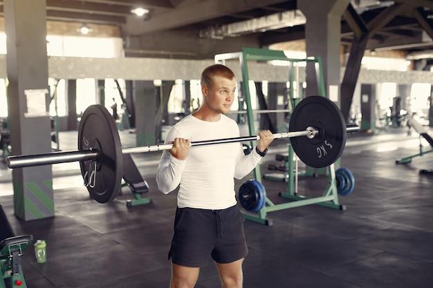 Bel homme s'entraînant dans la salle de gym