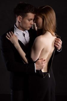 Le bel homme se concentre sur le retrait de la robe de la fille, qui l'embrasse doucement
