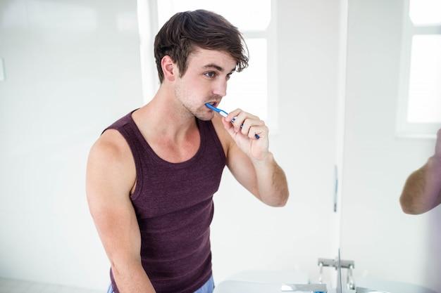 Bel homme se laver les dents dans la salle de bain