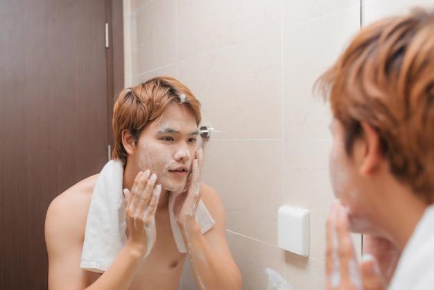 Bel homme se laver le visage dans la salle de bain