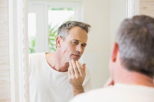 Bel homme se regardant dans le miroir de la salle de bain