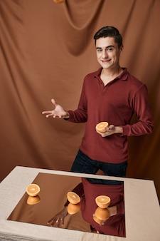 Bel homme se tient près de la table avec un miroir avec des oranges. photo de haute qualité