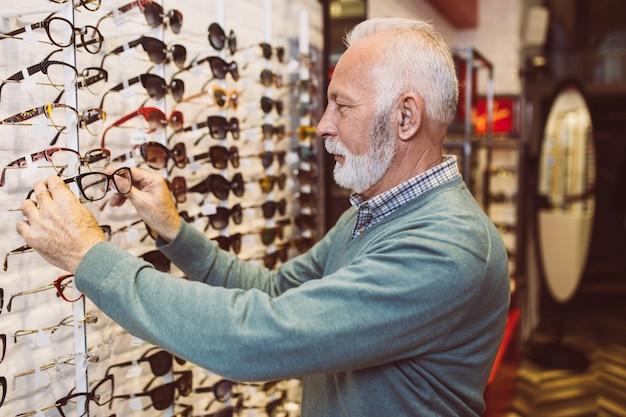Bel homme senior choisissant une monture de lunettes dans un magasin d'optique.