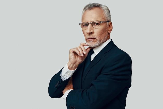Bel homme senior en costume complet regardant la caméra et gardant la main sur le menton en se tenant debout sur fond gris