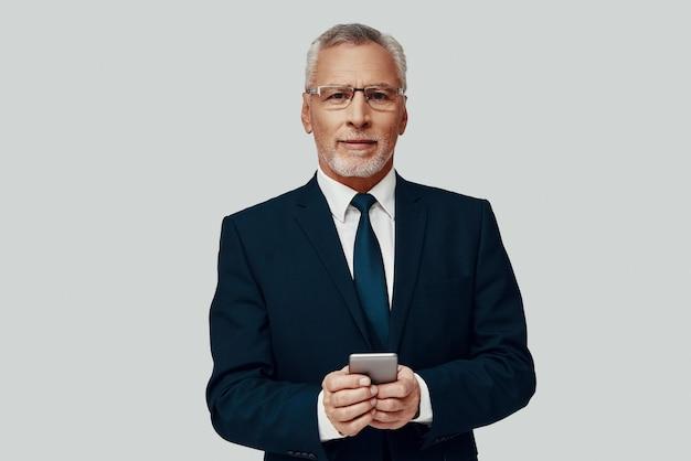 Bel homme senior en costume complet utilisant un téléphone intelligent et souriant en se tenant debout sur fond gris