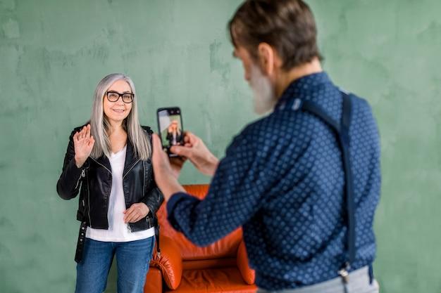 Bel homme senior faisant photo sur le téléphone pour sa belle femme aux longs cheveux gris