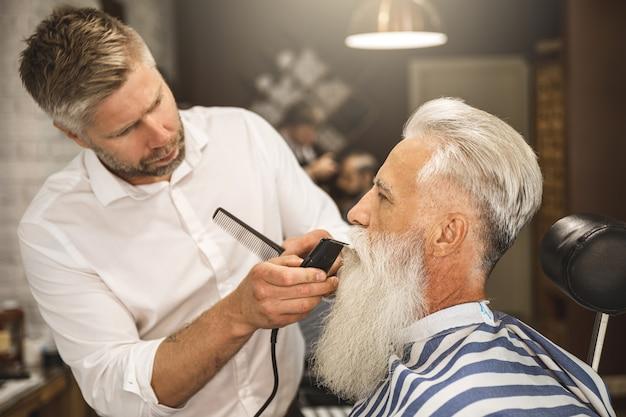 Bel homme senior se coiffant et taillant sa barbe dans le salon de coiffure