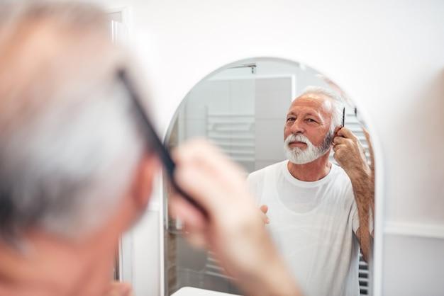 Bel homme senior se peignant les cheveux dans la salle de bain. concentrez-vous sur le reflet dans le miroir.