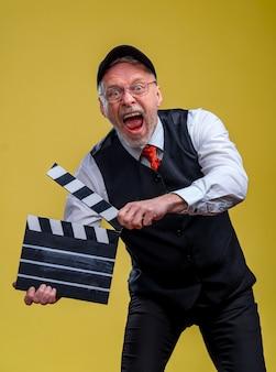 Bel homme senior tenant un battant de cinéma. homme portant un costume sans veste. personne isolée sur fond jaune. homme avec volet de film pendant le tournage