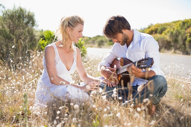 Bel homme sérénade sa copine avec guitare