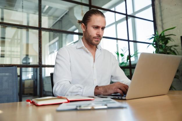 Bel homme sérieux avec des chaumes travaillant avec un ordinateur portable assis à table dans un bureau moderne