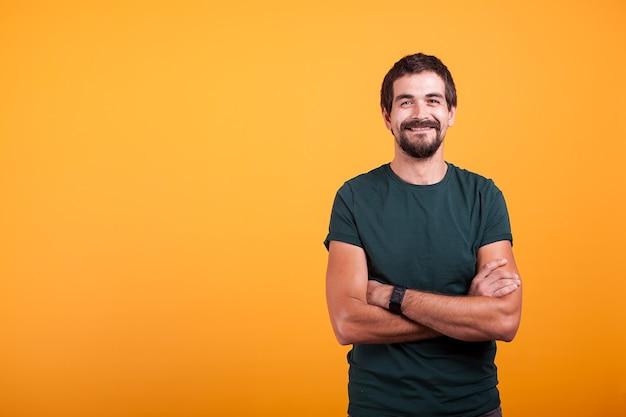 Bel homme avec ses bras croisés souriant à la caméra isolée sur fond jaune. portrait d'une personne confiante barbue attrayante en photo de studio