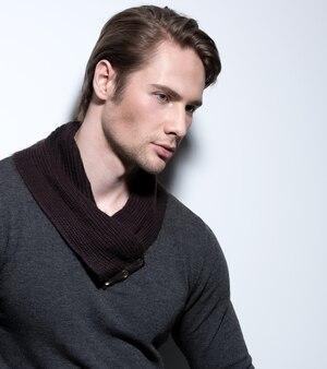 Bel homme sexy en pull gris pose sur le mur avec des ombres contrastées et regardant de côté.
