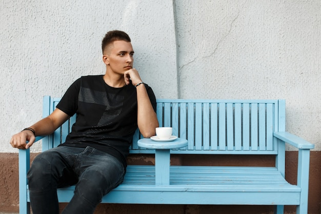 Bel homme solitaire est assis seul sur un banc et boit du café