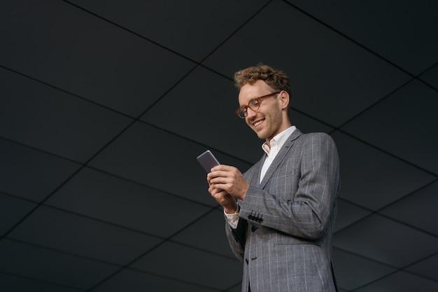 Bel homme souriant à l'aide de communication par téléphone mobile shopping en ligne debout sur la rue urbaine
