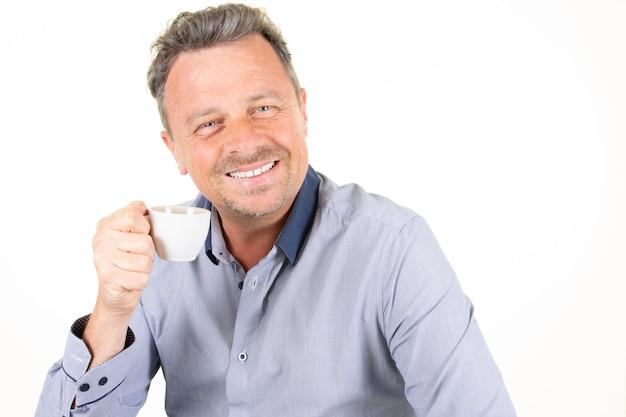 Bel homme souriant attrayant avec une tasse de café de boisson chaude à la main sur fond blanc