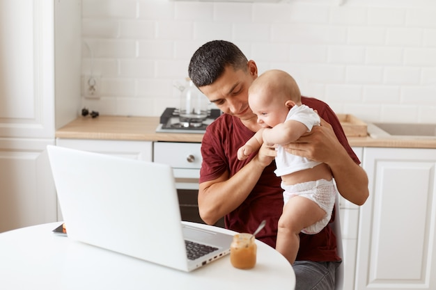 Bel homme souriant aux cheveux noirs portant un t-shirt décontracté bordeaux, travaillant sur un ordinateur portable tout en faisant du babysitting et en jouant avec sa fille, posant dans une cuisine blanche.