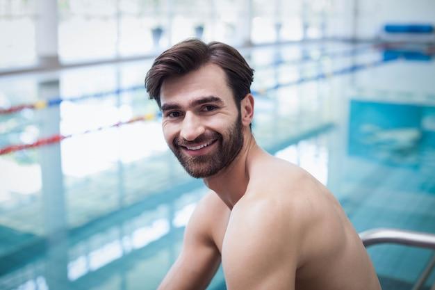 Bel homme souriant à la caméra à la piscine