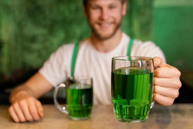 Bel homme souriant célébrant st. le jour de patrick avec des boissons