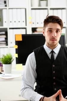 Bel homme souriant en costume-cravate stand in office